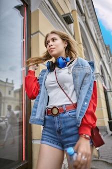 Mulher vestida em estilo de rua desce a avenida da cidade europeia.