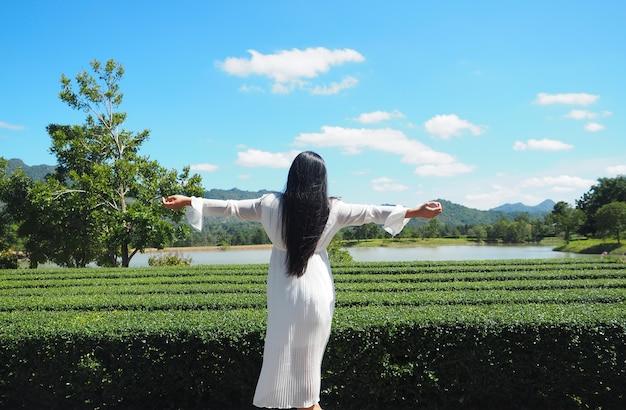 Mulher vestido branco alegre ficar na natureza e vista para a montanha rio lindo céu azul