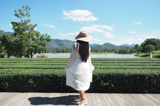 Mulher vestido branco com suporte para chapéu na natureza e vista para a montanha rio lindo céu azul