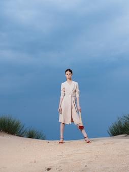 Mulher vestido de verão sapatos vermelhos machado areia natureza céu azul.