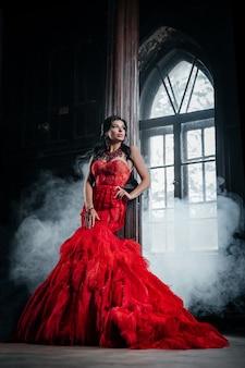 Mulher vestido vermelho vintage velho castelo linda princesa em vestido sedutor elegante caucasiana feminina história de conto de fadas perto de uma janela grande com névoa de fumaça