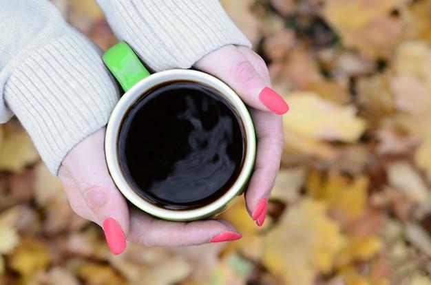 Mulher vestindo blusa branca, segurando uma xícara de café verde