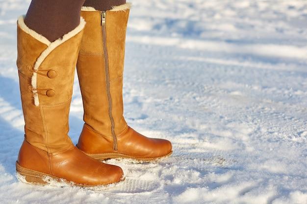 Mulher vestindo botas de inverno marrom na neve