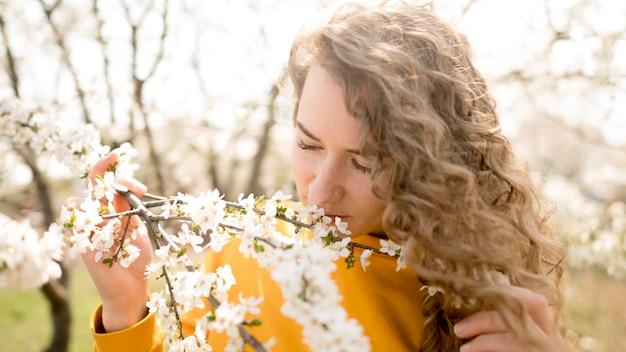 Mulher vestindo camisa amarela, cheirando flores