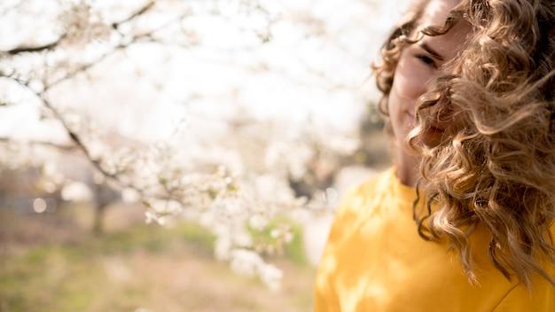 Mulher vestindo camisa amarela com galhos de flores
