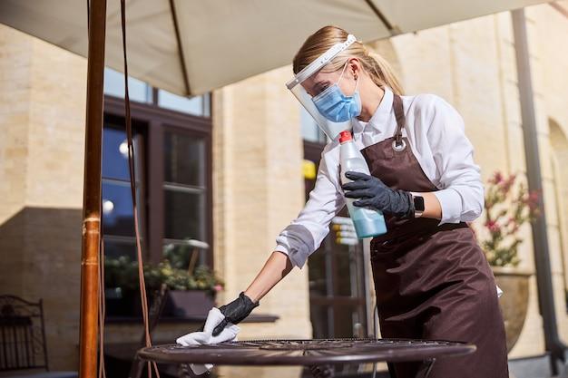 Mulher vestindo camisa branca e avental preparando restaurante ao ar livre