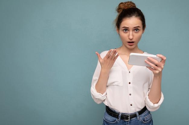 Mulher vestindo camisa casual branca e chapéu cinza isolado sobre uma parede de fundo azul segurando o telefone