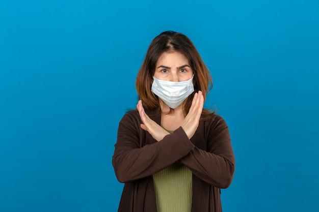 Mulher vestindo casaco de lã marrom na máscara protetora médica em pé com os braços cruzados, fazendo o gesto de parada com o rosto carrancudo sobre parede azul isolada