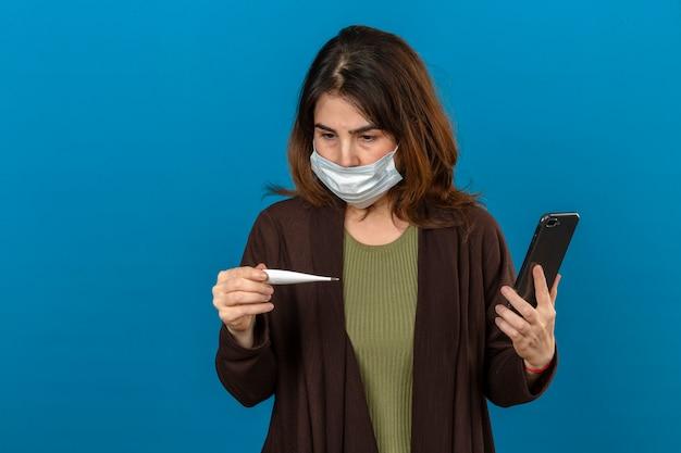 Mulher vestindo casaco de lã marrom na máscara protetora médica segurando o smartphone olhando termômetro digital na mão chamando para alguém olhando nervoso sobre parede azul isolada