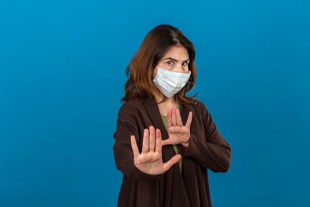 Mulher vestindo casaco marrom na máscara de proteção médica, segurando as mãos para cima dizendo não se aproxime sobre parede azul isolada