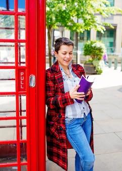 Mulher vestindo casaco vermelho, jeans e camisa branca, segurando o livro / caderno roxo inclinou-se contra a caixa de telefone vermelha
