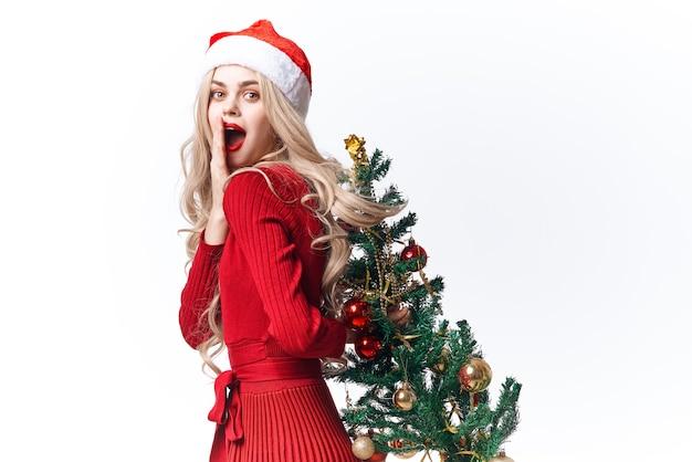 Mulher vestindo chapéu de papai noel decoração da árvore de natal luz de fundo do feriado. foto de alta qualidade