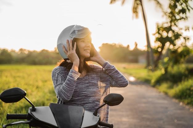 Mulher vestindo e aperte o capacete enquanto andava