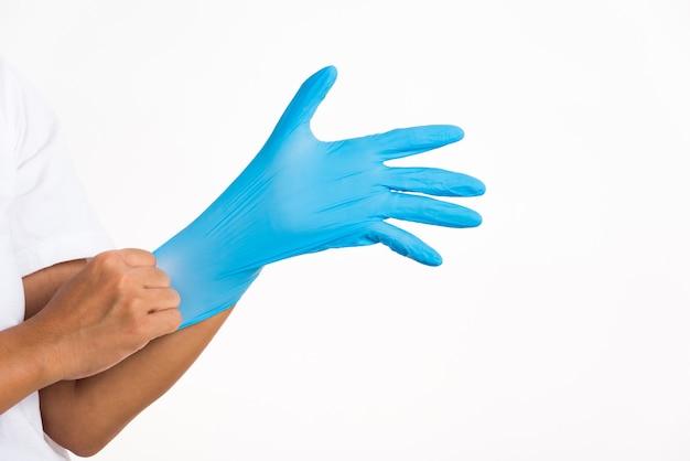 Mulher vestindo e colocando a mão em uma luva de látex de borracha azul para médico