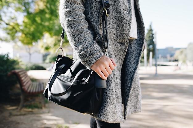 Mulher vestindo e posando com um casaco e bolsa na coleção de outono