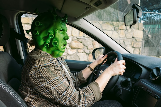 Mulher vestindo fantasia - máscara de coronavírus covid-19 dirigindo um carro