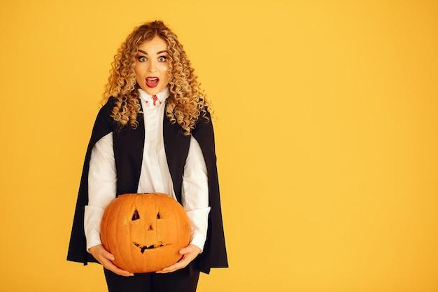 Mulher vestindo fantasia preta. senhora com maquiagem de halloween. garota de pé sobre um fundo amarelo.