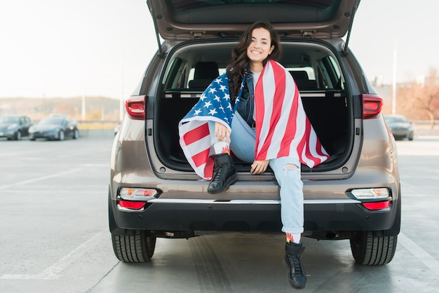 Mulher vestindo grande bandeira dos eua na mala do carro
