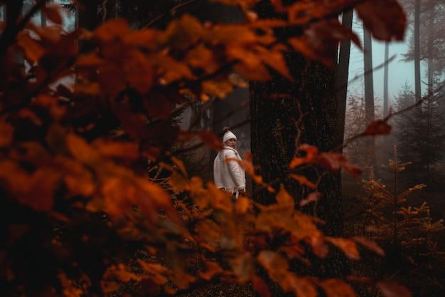 Mulher vestindo jaqueta branca em pé perto de uma árvore na floresta