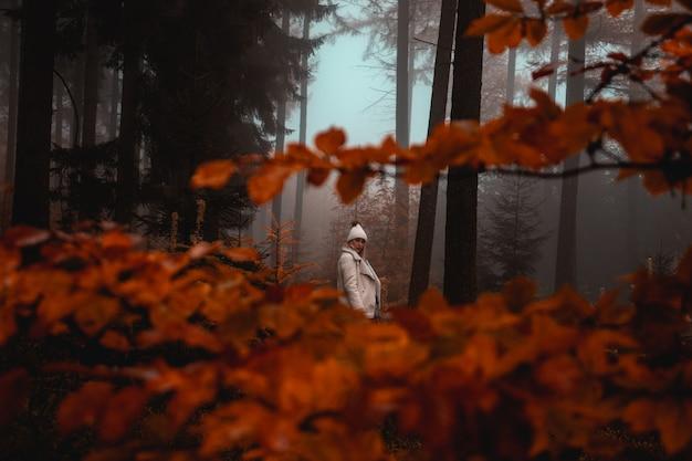Mulher vestindo jaqueta branca na floresta
