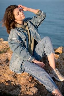 Mulher vestindo jaqueta jeans ao lado do mar