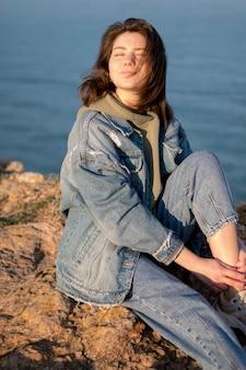Mulher vestindo jaqueta jeans ao lado do oceano
