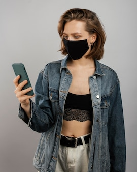 Mulher vestindo jaqueta jeans e máscara enquanto usa o celular