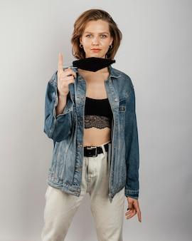 Mulher vestindo jaqueta jeans e máscara