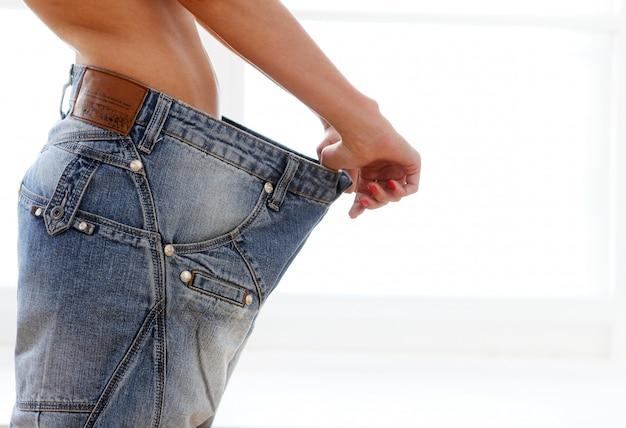 Mulher vestindo jeans após perda de peso