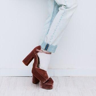 Mulher vestindo jeans e salto de veludo
