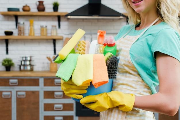 Mulher vestindo luvas de borracha amarela segurando produtos de limpeza em casa