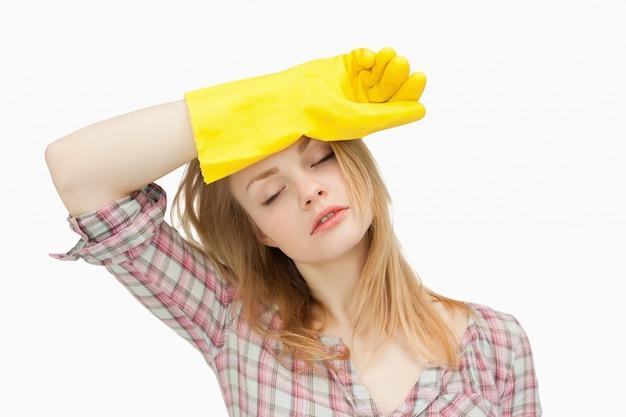 Mulher vestindo luvas de limpeza ao limpar a testa