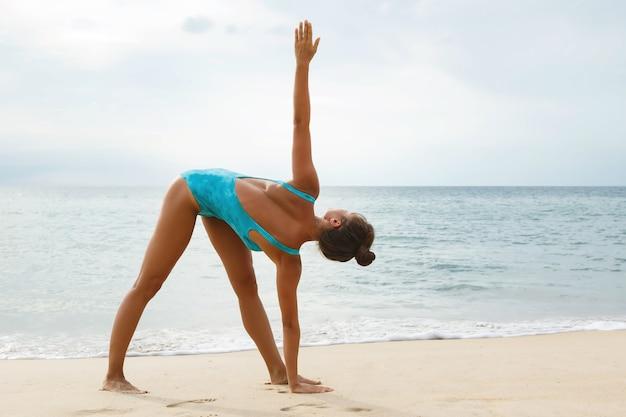 Mulher vestindo maiô azul fazendo exercícios de ioga na praia
