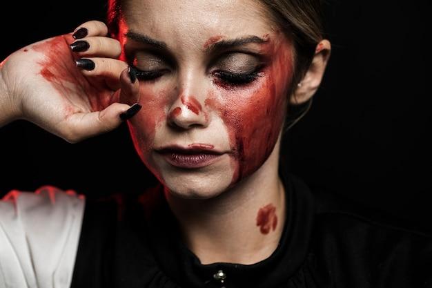 Mulher vestindo maquiagem sangrenta em fundo preto