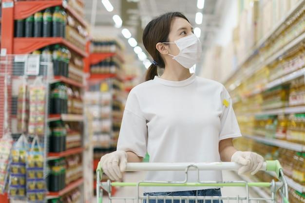 Mulher vestindo máscara cirúrgica e luvas com um carrinho de compras, comprando durante uma pandemia de coronavírus.