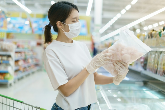 Mulher vestindo máscara cirúrgica e luvas, escolhendo peixe congelado no supermercado após pandemia de coronavírus.