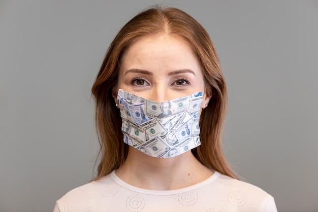 Mulher vestindo máscara cirúrgica feita de dinheiro