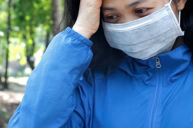 Mulher vestindo máscara e sentindo-se doente