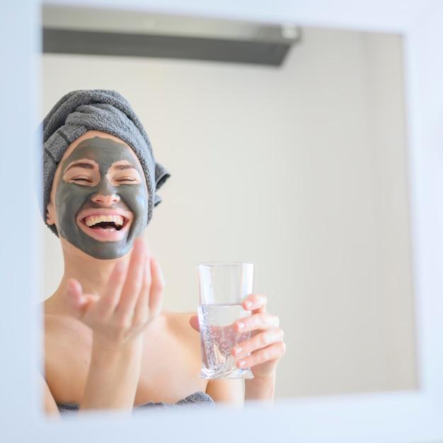 Mulher vestindo máscara facial sorrindo no espelho