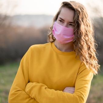 Mulher vestindo máscara médica e com as mãos cruzadas