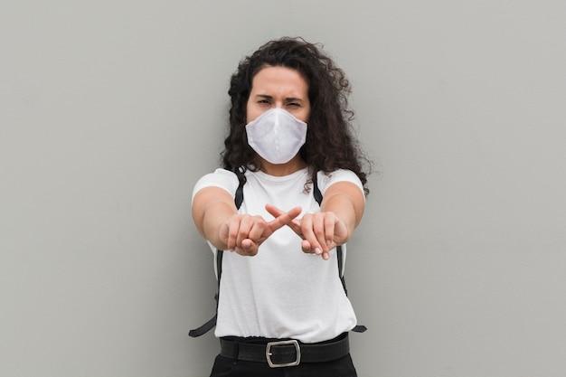 Mulher vestindo máscara médica e formando um x com os dedos