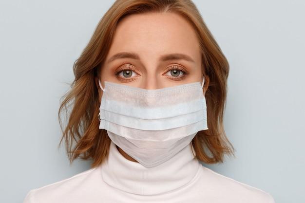 Mulher vestindo máscara médica, olhando. epidemia de gripe, alergia a poeira, proteção contra vírus. covid-19, coronavírus.