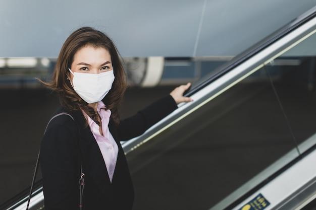 Mulher vestindo máscara na escada rolante.