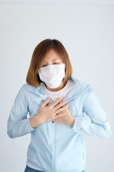 Mulher vestindo máscara protetora, colocando as mãos no peito