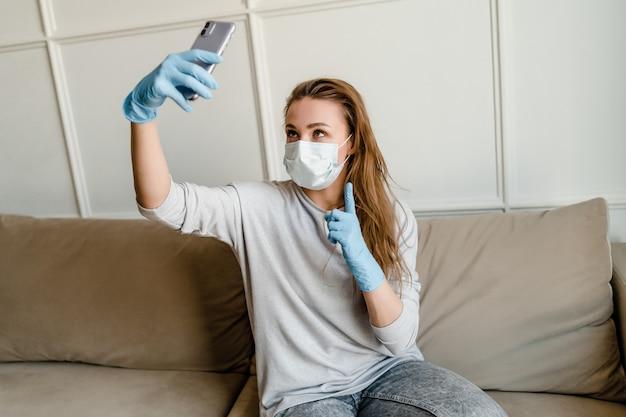 Mulher vestindo máscara protetora e luvas médicas usa telefone em casa