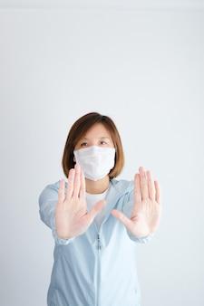 Mulher vestindo máscara protetora, fazendo um gesto de parada