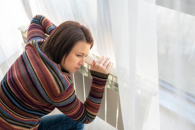 Mulher vestindo pulôver sentado perto de radiador aquecedor e abraça