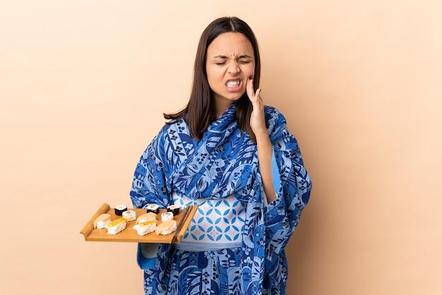 Mulher vestindo quimono e segurando sushi sobre parede isolada com dor de dente