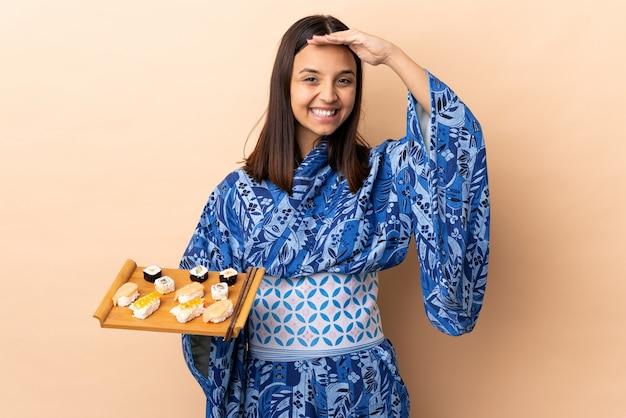 Mulher vestindo quimono e segurando sushi sobre parede saudando com mão com expressão feliz