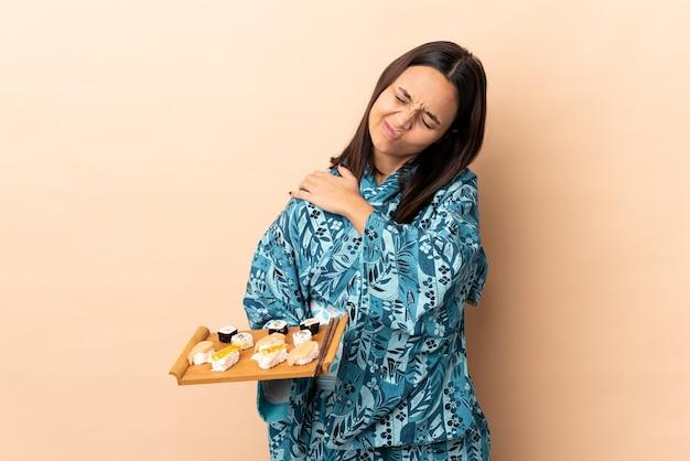 Mulher vestindo quimono e segurando sushi sobre uma parede isolada, sentindo dor no ombro por ter feito um esforço